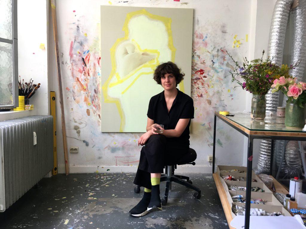 Die Malerin Vivien Greten sitzt vor einem ihrer Bilder in ihrem Atelier in Düsseldorf.